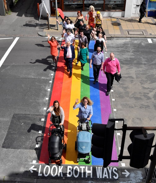 Excited pedestrians walking across the rainbow crossing